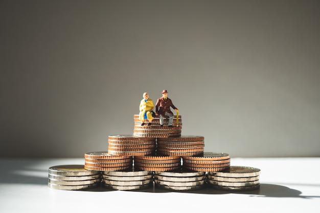 Miniaturleute, die älteren leute, die auf stapelmünzen sitzen als job-pensionierungskonzept sitzen
