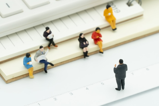 Miniaturleute, die auf anmerkungsbuch sitzen, setzten weißen hintergrund ein. besprechung oder diskussion