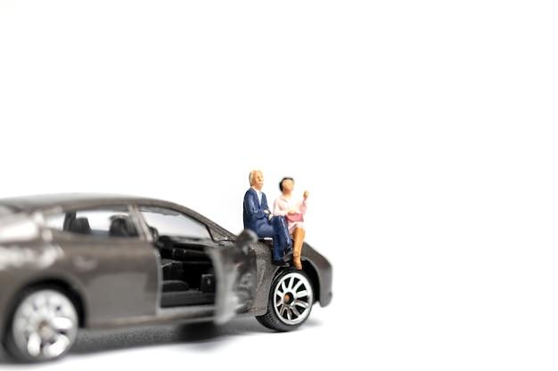 Miniaturleute, die auf auto mit kopienraum sitzen