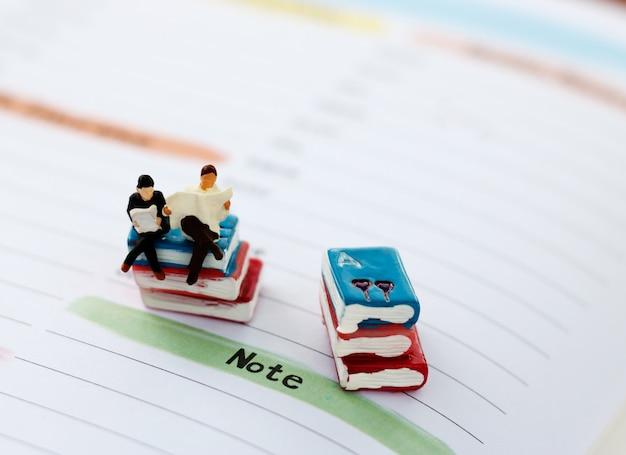 Miniaturleute, die auf buch lesen und sitzen.