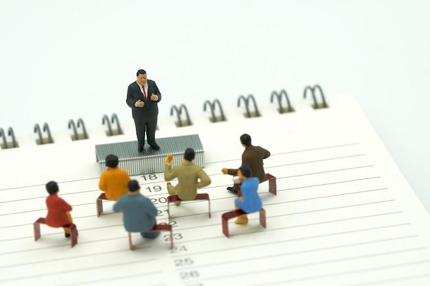 Miniaturleute, die auf den roten heftklammern gesetzt auf ein buch-klassifizierungen sitzen