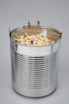 Miniaturleute, die auf dosen fischen