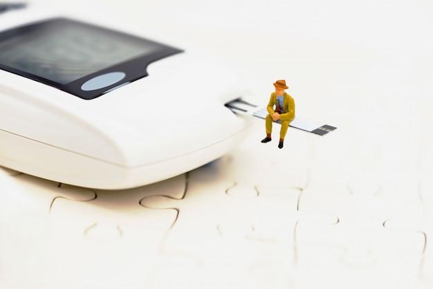 Miniaturleute, die auf einem glukosemeter von diabetes sitzen