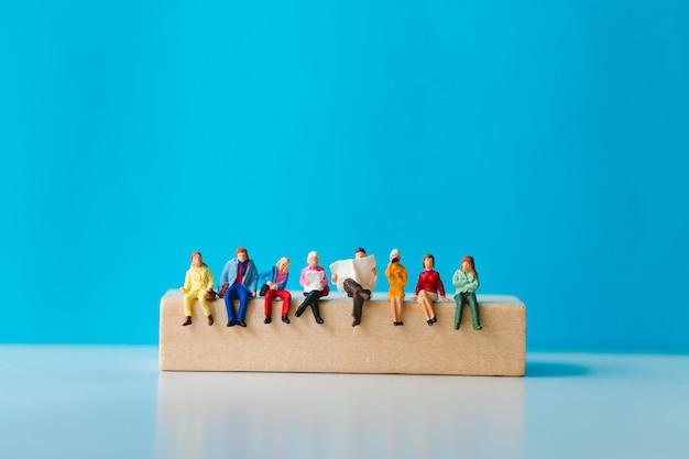 Miniaturleute, die auf holzklotz mit auf blauem hintergrund sitzen