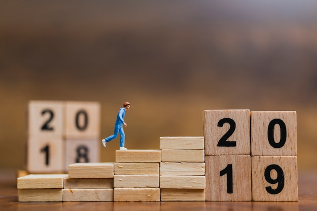 Miniaturleute, die auf holzklotz nr. 2019 laufen