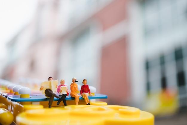 Miniaturleute, die auf minixylophon verwenden als soziales und geschäftstreffenkonzept sitzen