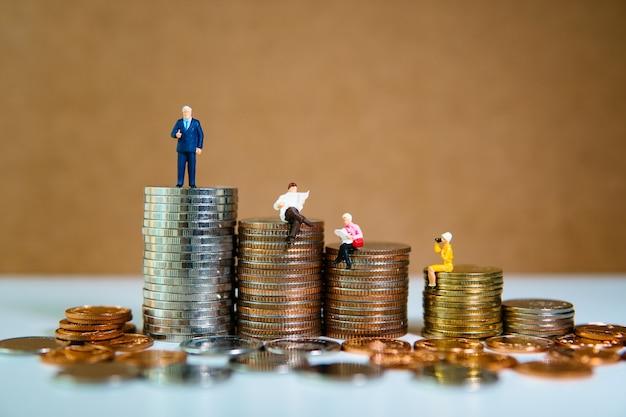 Miniaturleute, die auf stapel von münzen sitzen