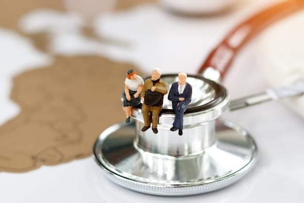 Miniaturleute, die auf stethoskop auf weltkarte sitzen.
