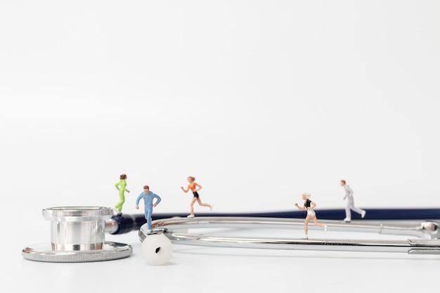 Miniaturleute, die auf stethoskop laufen