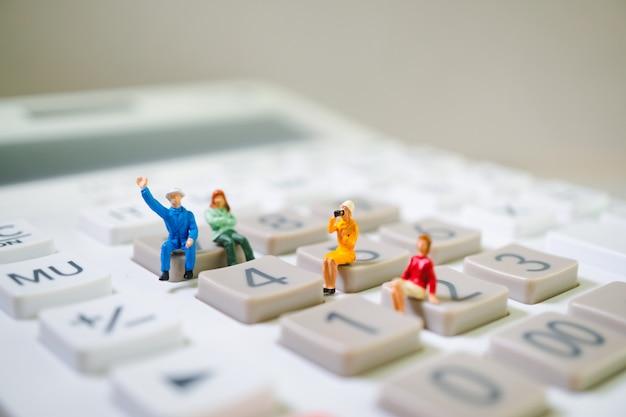 Miniaturleute, die auf taschenrechner sitzen