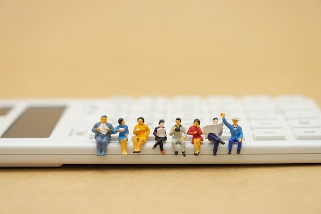Miniaturleute, die auf weißem taschenrechner sitzen