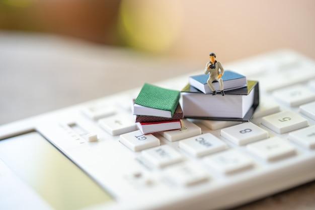 Miniaturleute, die auf weißem taschenrechner unter verwendung als hintergrundgeschäft sitzen