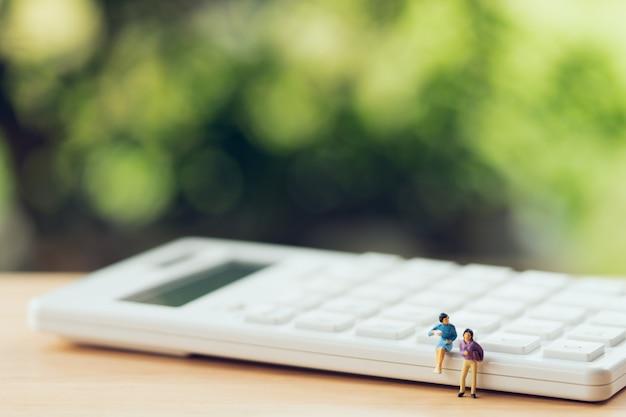 Miniaturleute, die auf weißem taschenrechner unter verwendung als hintergrundgeschäftskonzept sitzen