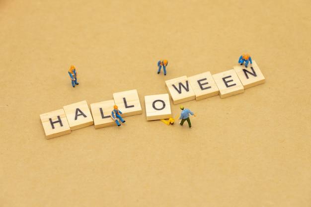 Miniaturleute, die mit hölzernem wort halloween unter verwendung als hintergrund universaltag stehen
