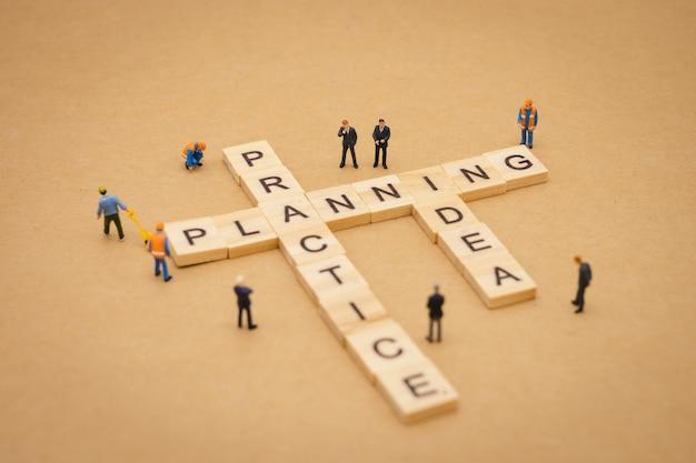 Miniaturleute, die mit hölzernem wort planung, praxis und idee stehen