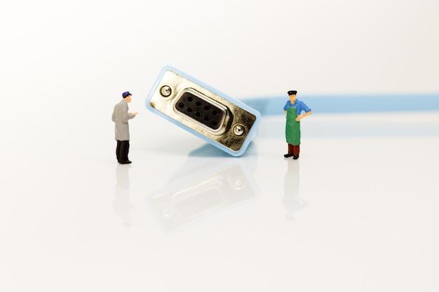 Miniaturleute, die mit konsolenkabel stehen.