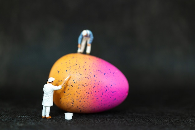 Miniaturleute, die ostereier für ostertag malen