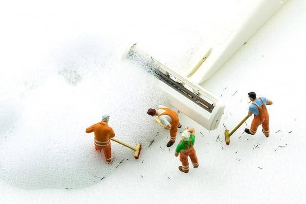 Miniaturleute, die schmutzigen weißen rasierapparat auf weißem hintergrund säubern.