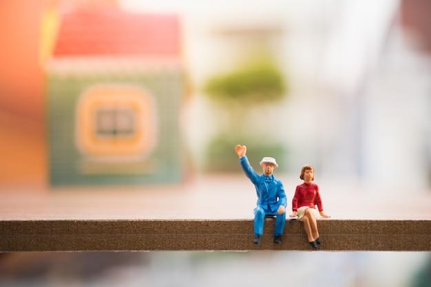 Miniaturleute, ehemann und frau, die vor dem haus verwendet als familienkonzept sitzen