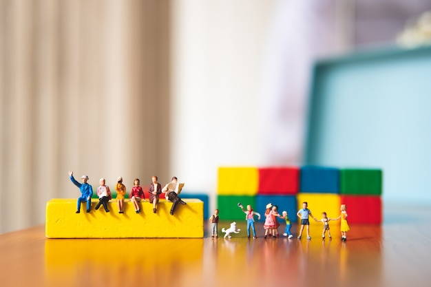 Miniaturleute, erwachsener und kinder mit hölzernem farbhintergrund