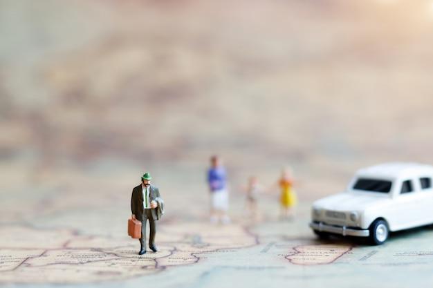 Miniaturleute: familie, die hand in hand mit auf weltkarte mit auto, glückliches familientageskonzept geht.