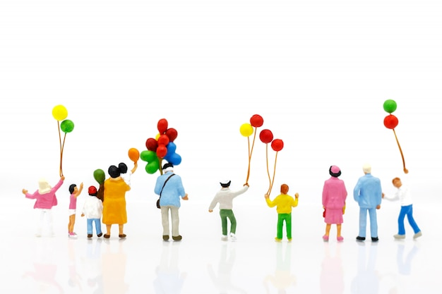 Miniaturleute: familie und kinder genießen mit bunten ballonen, glückliches familientageskonzept.
