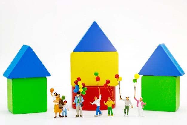 Miniaturleute: familie und kinder genießen mit bunten ballonen, holzklotz, glückliches familientageskonzept.