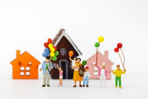 Miniaturleute: familie und kinder genießen mit bunten ballonen und haus, glückliches familientageskonzept.