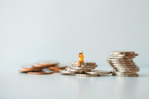 Miniaturleute, frau, die auf stapelmünzen unter verwendung als geschäft und finanzkonzept sitzt