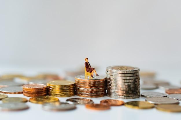 Miniaturleute, geschäftsfrau, die auf stapelmünzen unter verwendung als geschäfts- und finanzkonzept sitzt