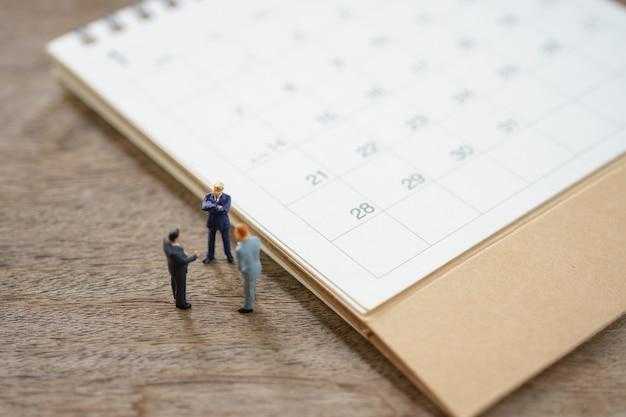 Miniaturleute-geschäftsleute, die auf weißem kalender stehen, als hintergrundgeschäftskonzept verwenden