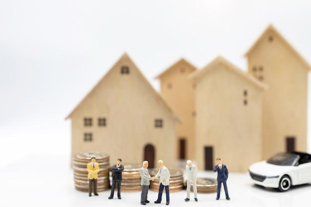Miniaturleute: geschäftsleute, die hände auf münzstapel mit haus und auto rütteln. konzept der investitionen in wohnungen und fahrzeuge.