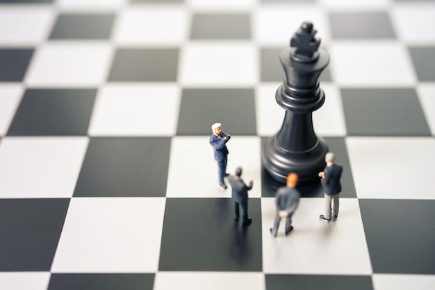 Miniaturleute-geschäftsmänner, die auf einem schachbrett mit einer schachfigur stehen