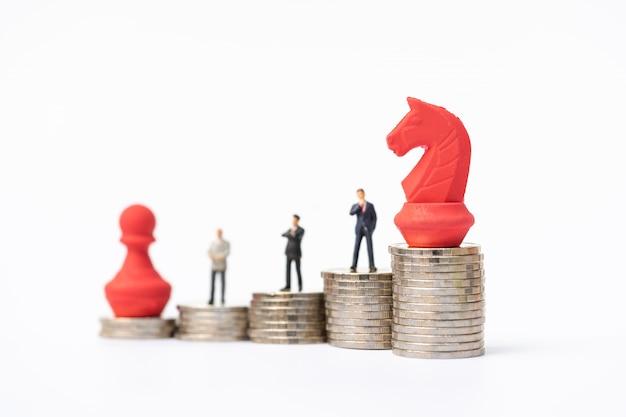 Miniaturleute, geschäftsmänner, die auf stapel münzen mit roter schachfigur stehen.
