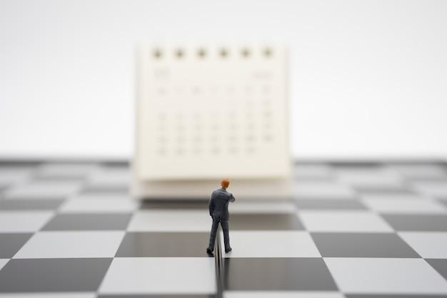 Miniaturleute-geschäftsmänner, die auf weißem kalender stehen