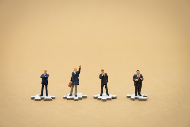Miniaturleute-geschäftsmänner, die auf weißer laubsäge stehen