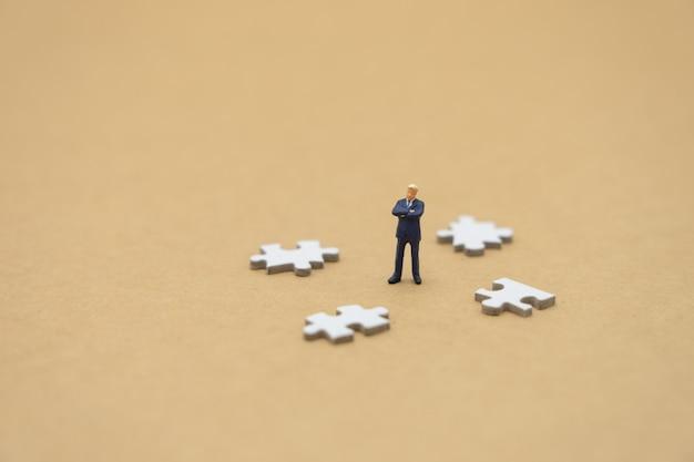 Miniaturleute-geschäftsmänner, die auf weißer laubsäge stehen.