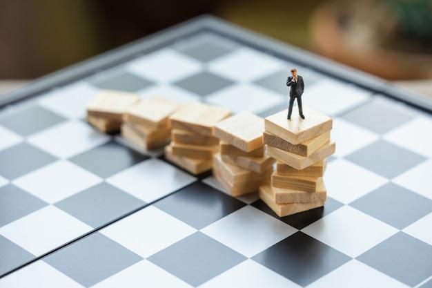 Miniaturleute geschäftsmänner, die investitionsanalyse oder investition stehen.