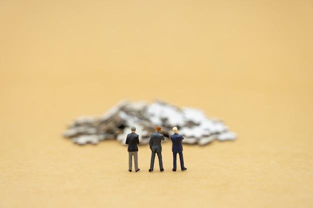 Miniaturleute-geschäftsmänner, die investitionsanalyse stehen oder in lösen investieren