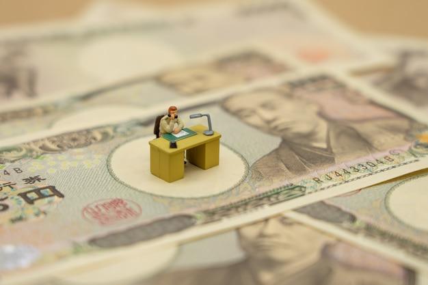 Miniaturleute-geschäftsmänner, die mit japanischen banknoten im wert von 10.000 yen sitzen