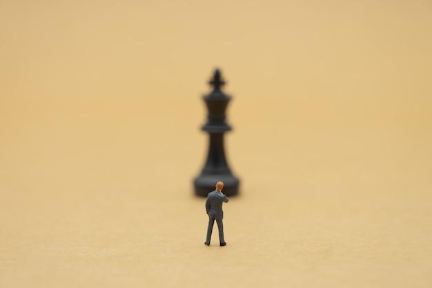 Miniaturleute-geschäftsmänner, die schach-analyse stehen, teilen über geschäft mit