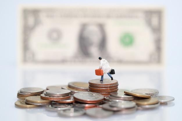 Miniaturleute: geschäftsmann, der auf dem stapeln von münzen steht