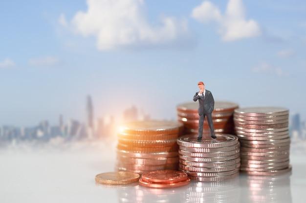 Miniaturleute: geschäftsmann, der auf der münze stapelt podium steht