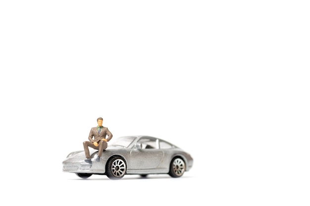 Miniaturleute-geschäftsmann, der auf einem auto sitzt und raum für text kopiert