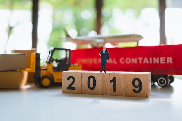 Miniaturleute, geschäftsmann, der auf holzklotz 2019 mit logistischem fahrzeug steht