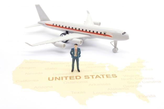 Miniaturleute, geschäftsmann, der auf karte amerikaner steht