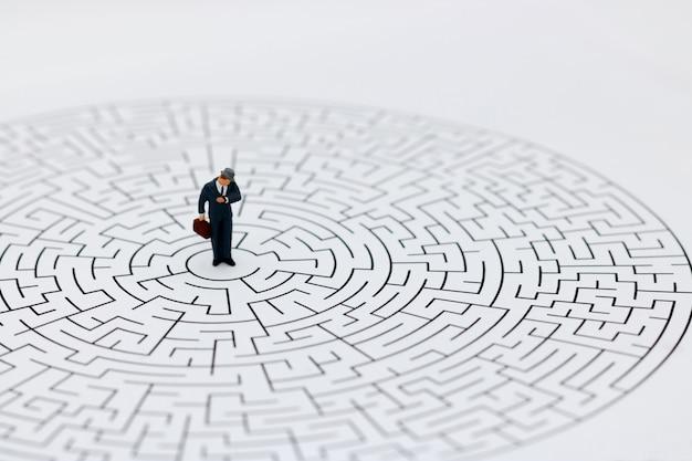 Miniaturleute: geschäftsmann, der auf mitte des labyrinths mit blick auf uhr steht.