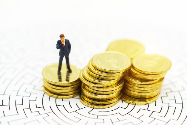 Miniaturleute geschäftsmann, der auf mitte des labyrinths mit münzenstapel steht.
