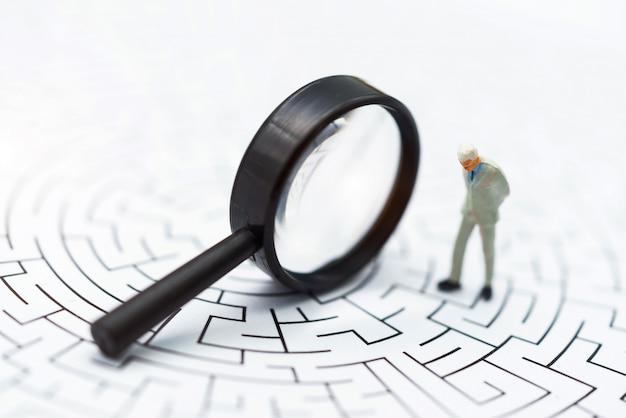 Miniaturleute, geschäftsmann, der auf mitte des labyrinths mit münzenstapel steht