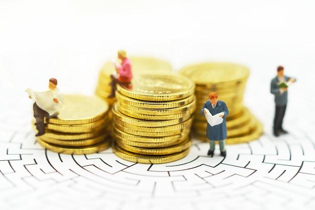 Miniaturleute: geschäftsmann, der auf mitte des labyrinths mit münzenstapel steht.